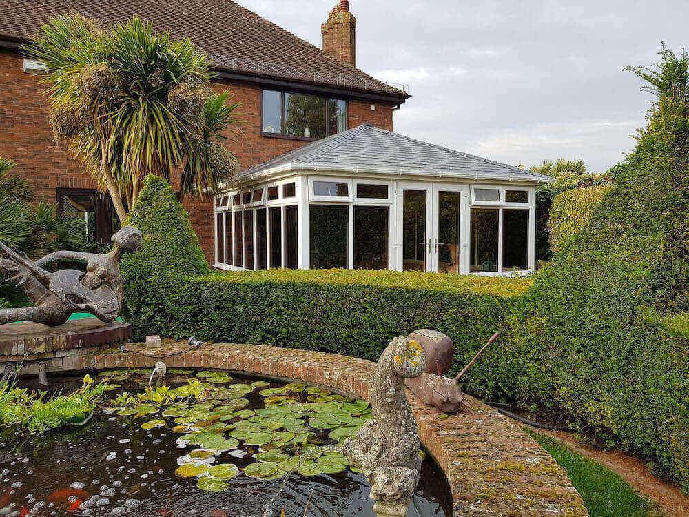 A black tiled roof on a white upvc conservatory.