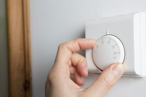 A hand turning down a white thermostat