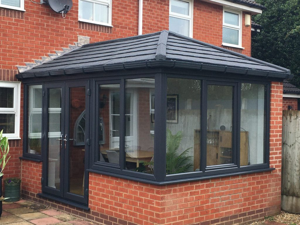 a black conservatory with french doors and a tiled roof
