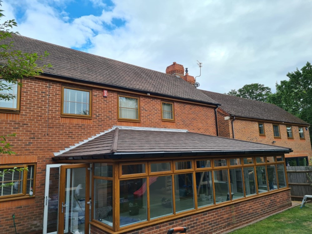 An after image of conservatory refurbishment with new tiled roof and white frames