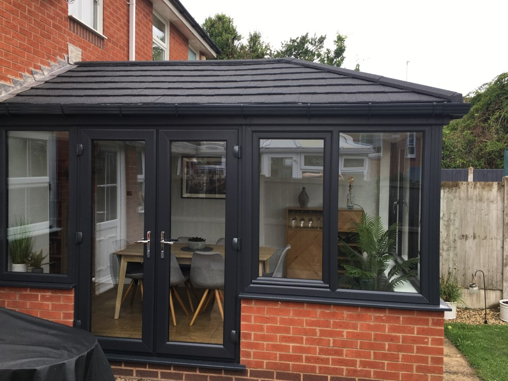 A Black PVC conservatory with french doors and tiled roof